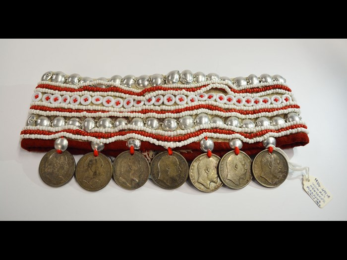 Forehead band of woman's hat of cream cotton fabric decorated with buttons, beads, tin studs, and silver rupee coins: Asia, South East Asia, North Thailand, Chiangrai, Lawle, Amphur Maechan, Akha people, by Mina, 1984.