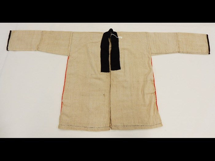 Woman's white cotton jacket with applique cotton borders and rows of fishtail overcasting in wool, worn under a black jacket: Burmese, North Thailand, Chiangrai, Lawle or Amphur Maechan, c. 1984.