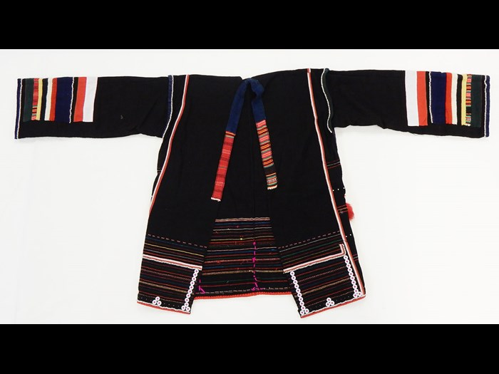 Woman's jacket of black cotton decorated with stripes in red, white, blue and yellow applique, ornamented with buttons, tin studs, cowrie shells, coins, and monkey fur tufts: Asia, South East Asia, North Thailand, Chiangrai, Hweisan or Amphur Mackon, Akha people, by Angoe, 1984.