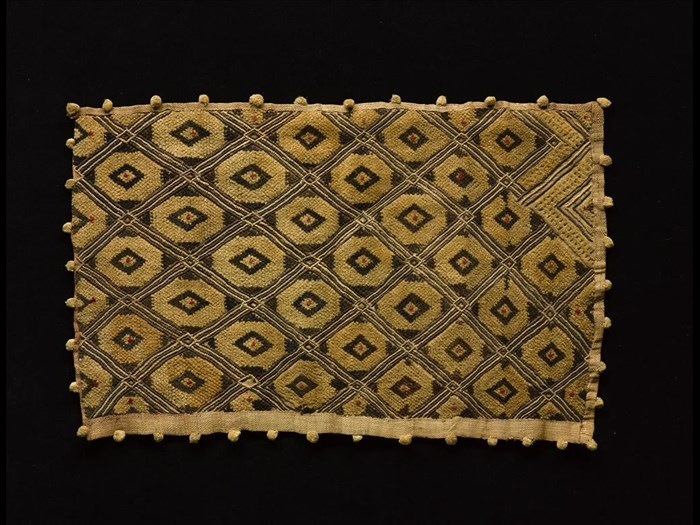 Rectangular raffia cloth, decorated with cut pile lozenge pattern, in three colours on a natural ground, border with small pom-poms at intervals: Africa, Central Africa, Democratic Republic of the Congo, Kasai, early 20th century.