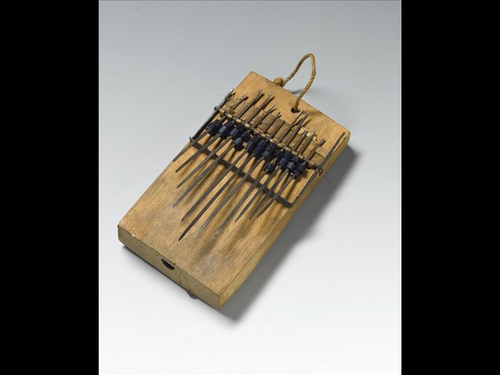 Thumb piano or likimbe, a hollowed wooden box with vibrating iron tongues, decorated with blue glass beads: Africa, Central Africa, Democratic Republic of the Congo, Lokombe, early 20th century.