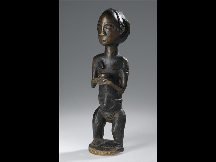 Carved wooden standing female figure  with dressed hair and body scarification, holding a jar with both hands: Africa, Central Africa, Democratic Republic of the Congo, Katanga, late 19th century.