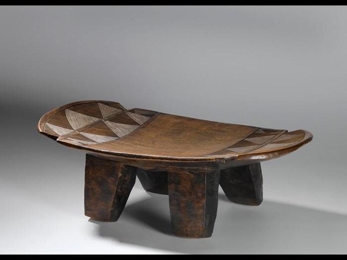 Slightly curved oblong wooden stool on four legs, with carved linear ornament: Africa, Southern Africa, Zambia, Tanganyika Plateau, Awemba, late 19th century.