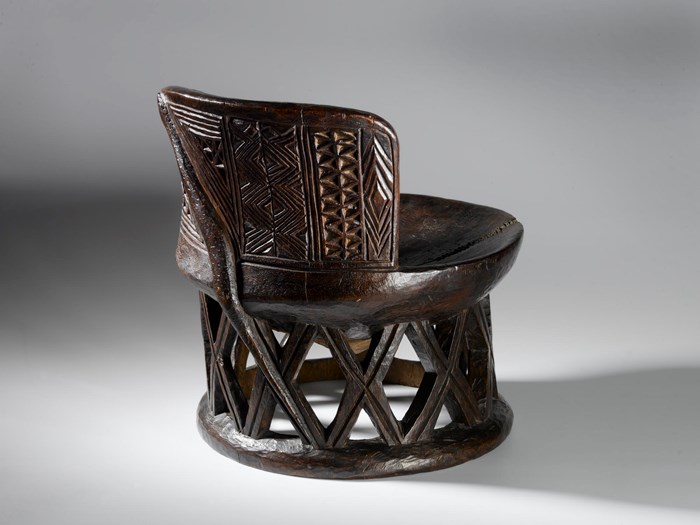Circular wooden stool with wire repair on seat, curved back and open lattice-work base, carved geometric patterns on seat back and serpent carved on back of stool from top to base: Africa, Central Africa, Democratic Republic of the Congo, Tanganyika Plateau, Bemba people, late 19th century.