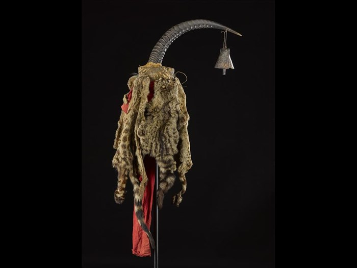 Antelope horn decorated with an iron bell, Palm Civet (Nandinia binotata) skins and a length of red cotton cloth, attached to a woven basket core, known as a lilamfia, used for divination in warfare: Africa, Southern Africa, Zambia, Tanganyika Plateau, Awemba, late 19th century.