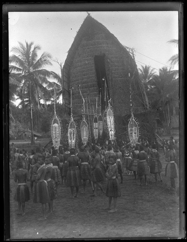 A group of Elema people, standing in front of a thatched roof men's house, all wearing plant fibre skirts, neck ornaments, and nose ornaments, with several people holding hevehe (masks); Purari Delta, Papua New Guinea. © The Trustees of the British Museum (CC BY-NC-SA 4.0)