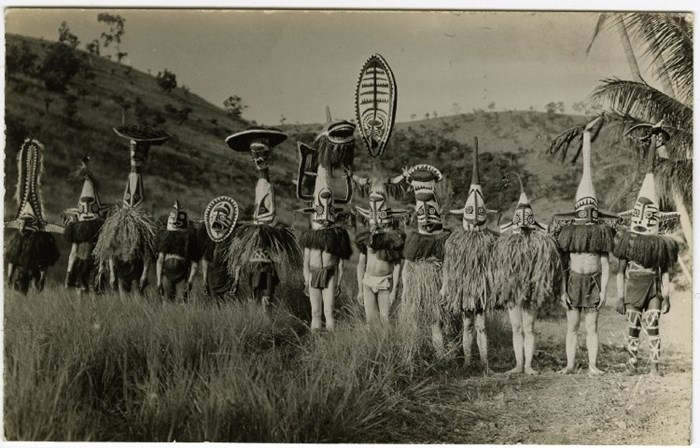 Postcard showing thirteen young men outdoors wearing eharo masks; they also wear plant fibre shoulder coverings and cloth wraps, as well as having thier bodies painted; grass and hills behind them; Purari Delta; Papua New Guinea. © The Trustees of the British Museum (CC BY-NC-SA 4.0)