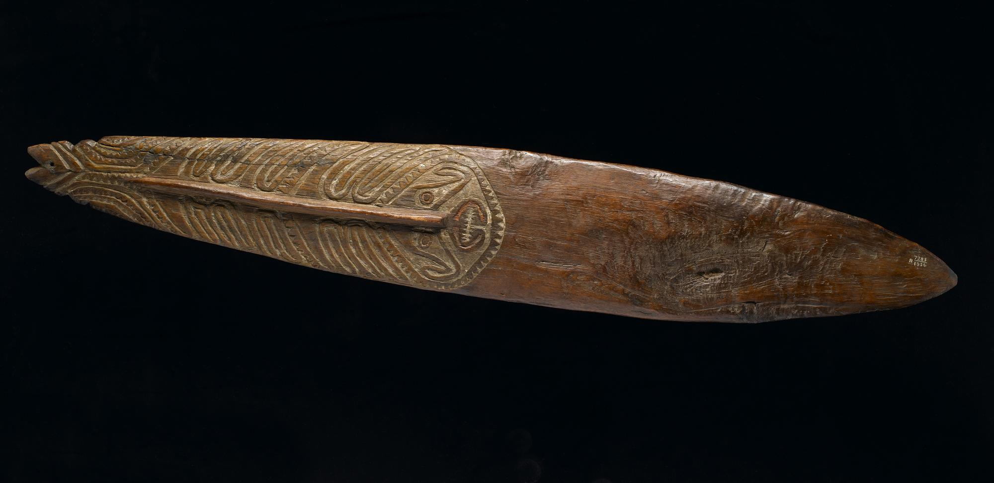 Bullroarer made of wood, carved with designs, including a human face, and decorated with pigment: Oceania, Melanesia, Papua New Guinea, Gulf Region, 19th century.