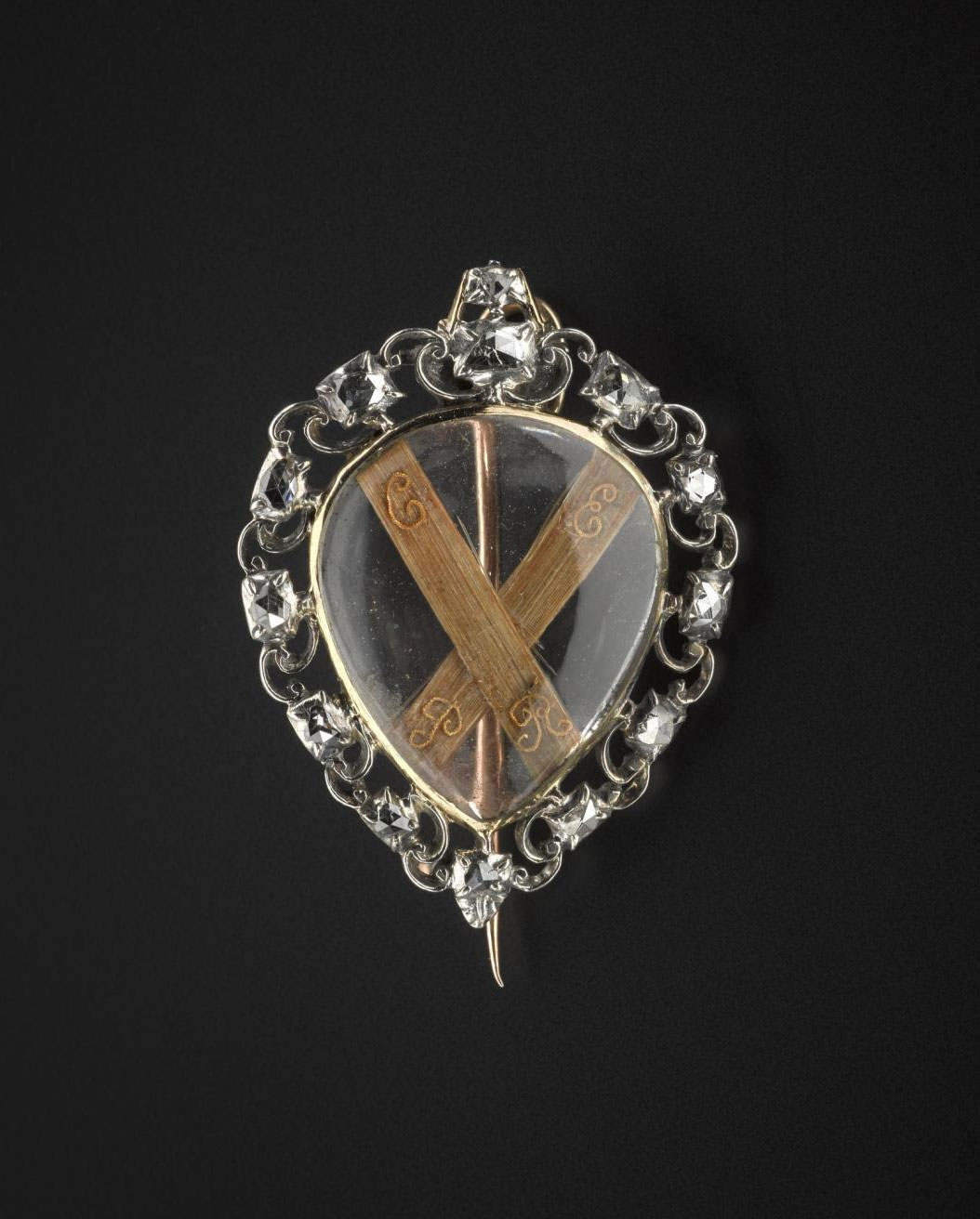 Heart-shaped brooch said to contain the hair of Prince Charles Edward Stuart and given to him by Lady Mary Clark. The hair forms the shape of a saltire with wire lettering 'C.E.P.R'.