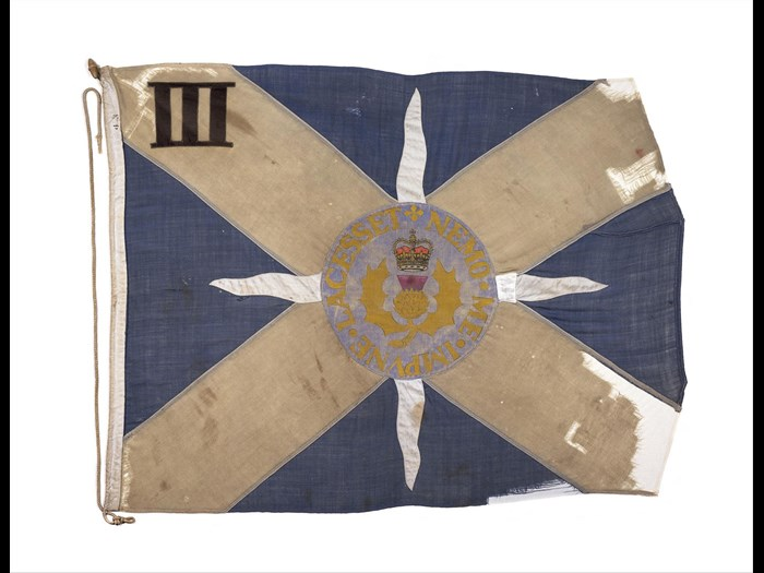 Company flag, Saltire with thistle and crown at centre and motto NEMO.ME.IMPVNE.LACESSET, flown while the battalion was serving in Northern Ireland, c.1975. On display in the National War Museum.