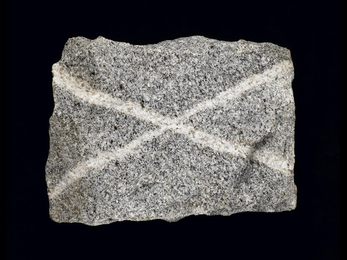 Grey granite with quartz veins, forming a saltire, from Persley Quarry, Aberdeen, Scotland. On display in the Scotland: A Changing Nation gallery at the National Museum of Scotland.