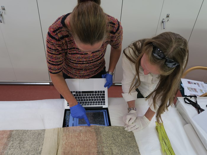 A. Denner and F. Reilly in the National Museum of Ireland stores comparing barkcloth NMI 1881.2651 with image of the National Museums Scotland piece on a laptop screen