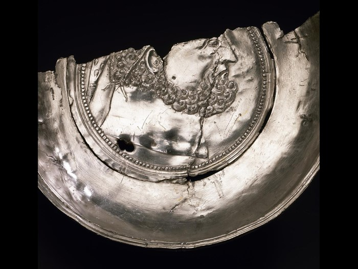 Half of a shallow silver bowl decorated with the head of Hercules, and featuring hunting scenes on the outside, from Traprain Law, East Lothian, AD 410–425.