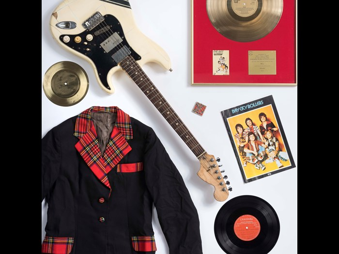 'Bay City Rollers jacket, 1976 tour programme, supersonic floppy disc and fan club badge on loan from a private collection; Bay City Rollers gold disc, guitar and earliest unreleased Bay City Roller acetate recording on loan from a private collection.