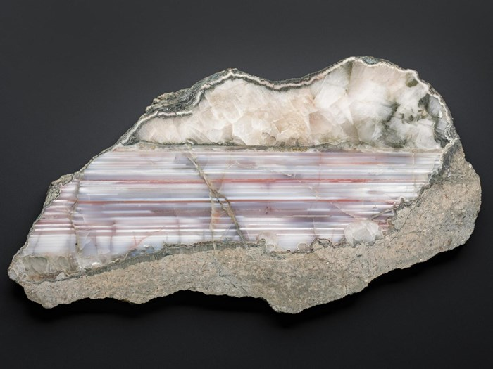Quartz, variety agate - a slice - grey, white and reddish-brown banded, with onyx - associated with common quartz and edged with rock matrix - polished on one face - from Dunure, Ayrshire