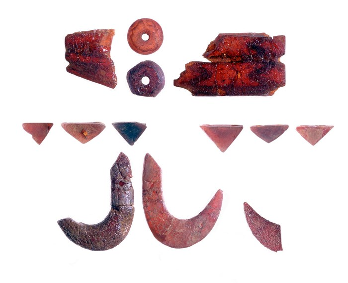 Some of the amber items found with the gold discs. Top: plates and beads from a spacer-plate necklace; bottom: prismatic V-perforated beads and hook-shaped ornaments, whose lack of wear suggests that they had probably been sewn onto a garment