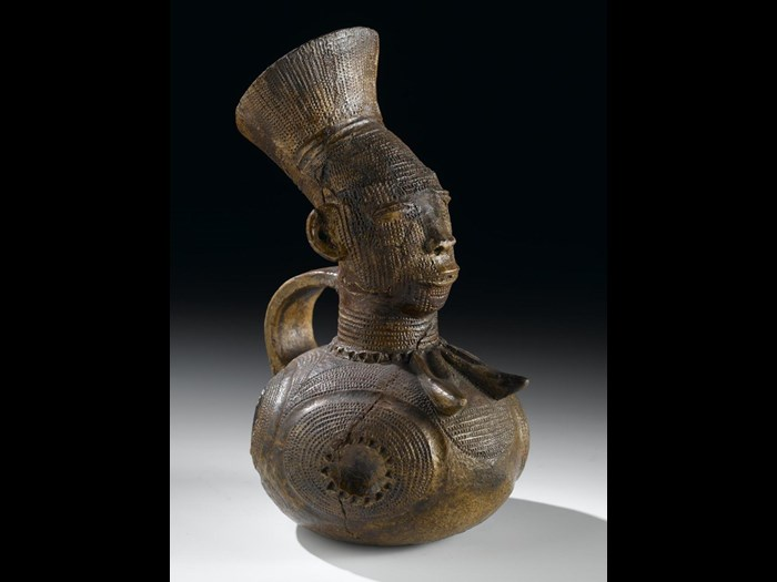 Early 20th century hand-modelled clay jug  from the Democratic Republic of the Congo, in the form of a high status Mangbetu woman with elaborate hairstyle and body decoration.