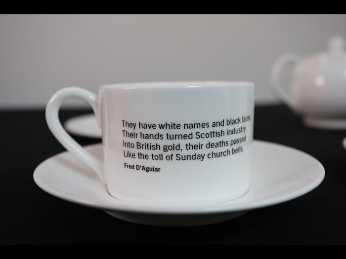 Porcelain teacup with poetry extract, from The Empire Café. At the pop up café in Glasgow, during the Commonwealth Games in 2014, visitors discussed new understandings of Scotland's slavery past over the products of empire. National Museums Scotland, X.2017.89.4.