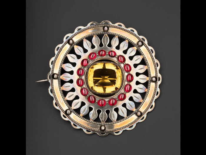 Silver plaid brooch set with a cairngorm in the centre and a ring of sixteen carbuncles round it, worn by the chiefs of Clanranald, mid-19th century.