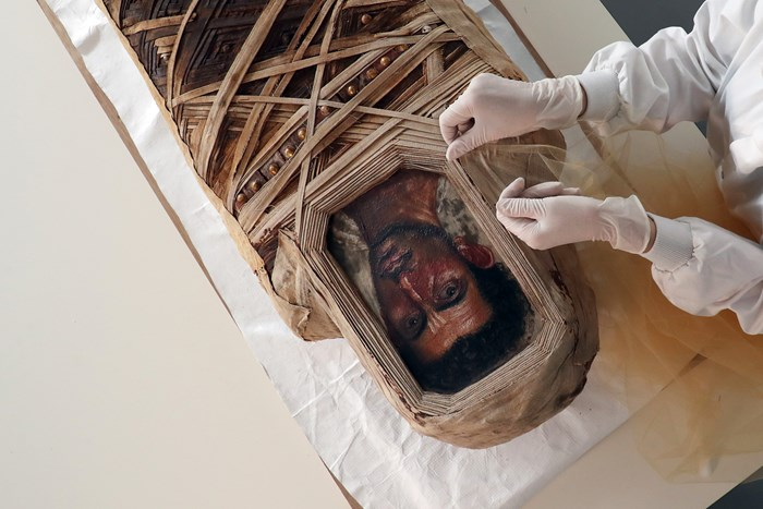 A mummified man is carefully conserved ahead of going on display in the new Ancient Egypt Rediscovered gallery.