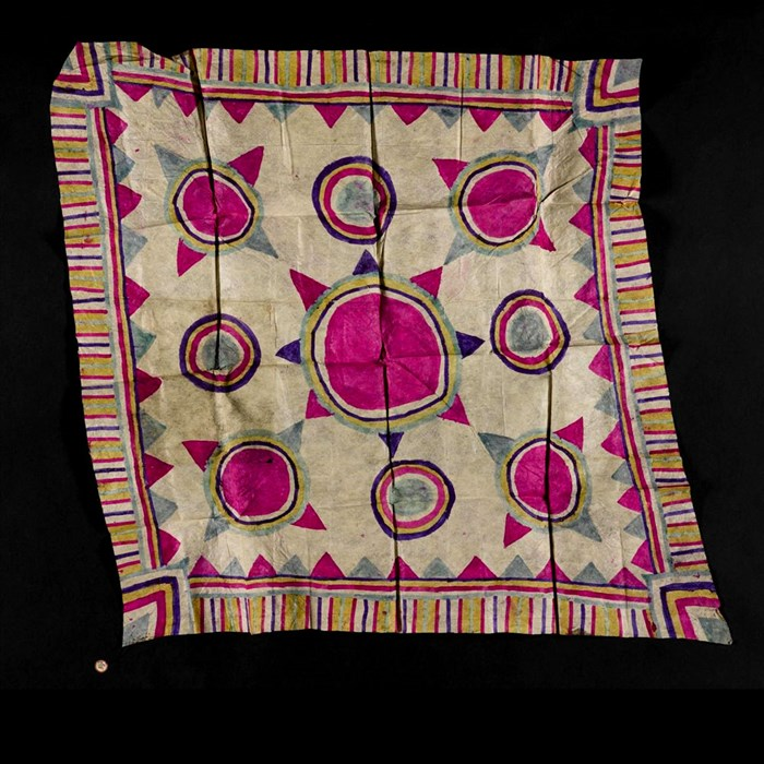 A textile square with pink circles and abstract patterns