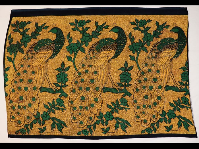 Capulana featuring a repeating pattern of large green and blue stylised peacocks on golden yellow ground: Africa, Southern Africa, Mozambique, 1994-2000.