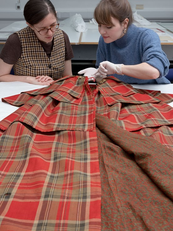 Research fellow Rosanne Waine and textile conservator Rosie Nuttall examine a stylish tartan cloak, a new acquisition that will feature in the exhibition.