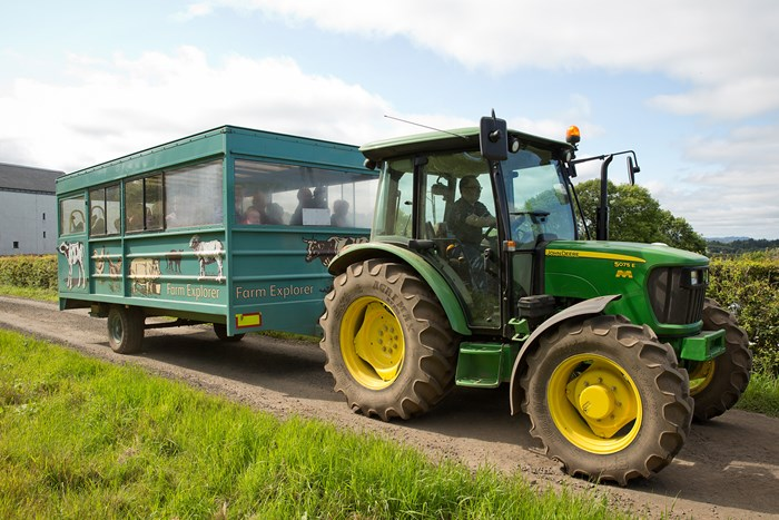A tractor in a field pulling a trailer