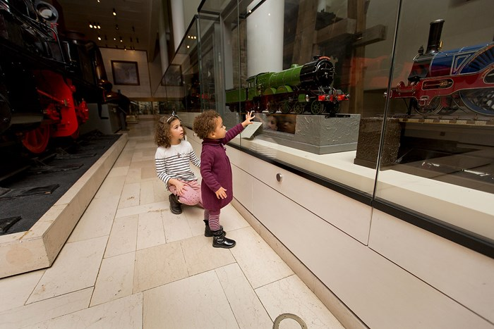 Two small children looking at a working steam engine model in the Industry and Empire gallery