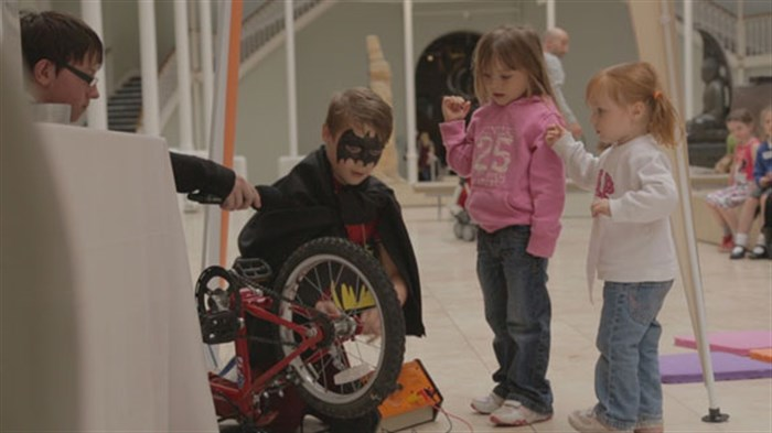 Helping Batman fix his bike in the Super Science Sleepover