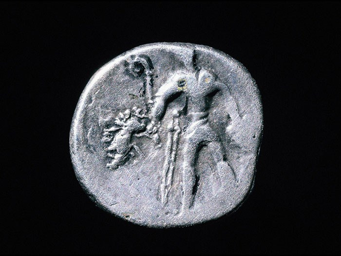 Gaulish coin showing a warrior carrying a carnyx, boar standard and severed head.