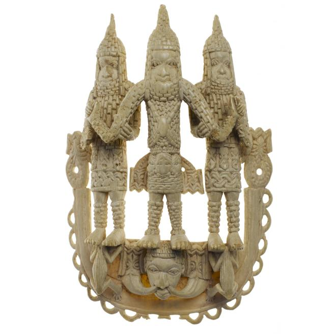 18th century U-shaped pendant of carved elephant ivory depicting an Oba flanked by his two attendants who support him at the elbows in a characteristic pose. The royal triad wear official regalia including deep coral neckbands and patterned kilts and the king is identified by the large bead of Kingship. Below the figures is a mudfish which refer to the Oba's dual identity as Olokun the water god.
