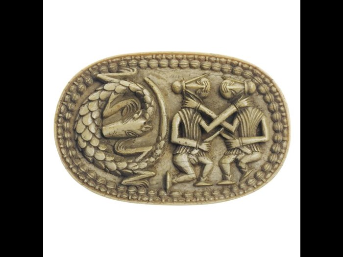 Early 19th century oval box lid of elephant ivory, carved with representations of two fighting Portuguese soldiers alongside a coiled pangolin.