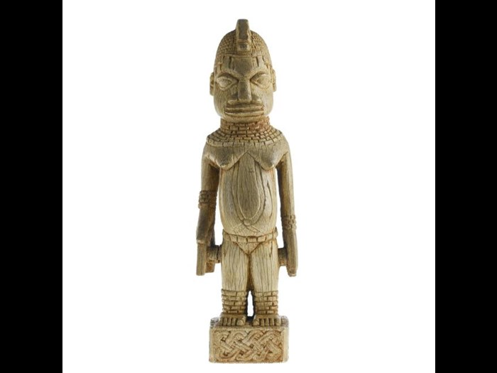 18th or 19th century figure of a female attendant in carved elephant ivory wearing coral beads and carrying an object representing either a double gong or a manilla.