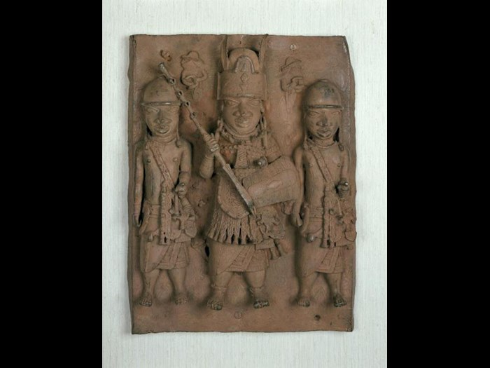 Bronze plaque made in the early 17th century showing a central figure of an Oba or chief flanked by two attendants, with two smaller Portuguese figures in the background, probably hung on the palace wall at the court in Benin.