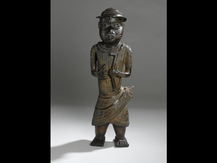 17th or 18th century cast brass figure of a royal messenger wearing a brimmed hat, fringed chest covering, wrapper and bracelets, and holding a blacksmith's hammer.