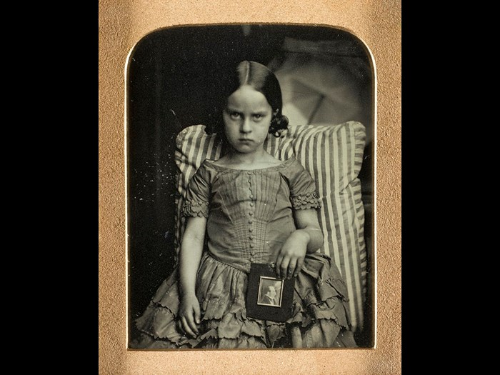 Unknown little girl sitting on a striped cushion holding a framed portrait of a man, possibly her dead father, by Ross & Thomson of Edinburgh,1847-60, ninth-plate daguerreotype.