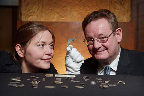 Alice Blackwell, The Glenmorangie Research Fellow and Hamish Torrie, Director of Corporate Social Responsibility at The Glenmorangie Company  examine a crescent shaped brooch fragment from the Roman Silver Hoard found in Aberdeenshire. Photo by Phil Wilkinson.