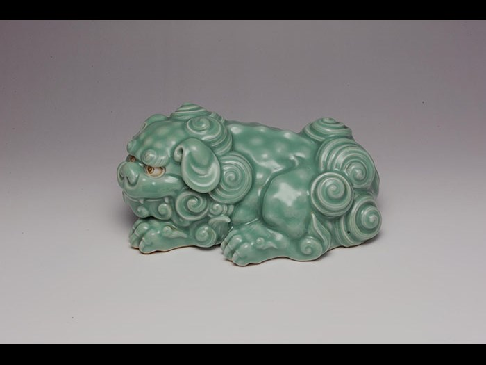 Sculpture of recumbent lion-dog (shishi) with celadon glaze, by Makuzu Kozan I, 1900-10.