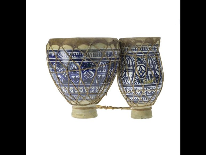 This tbilat or double drum is earthenware with a white tin oxide glaze, and painted in blue with bands of stylised foliage.
