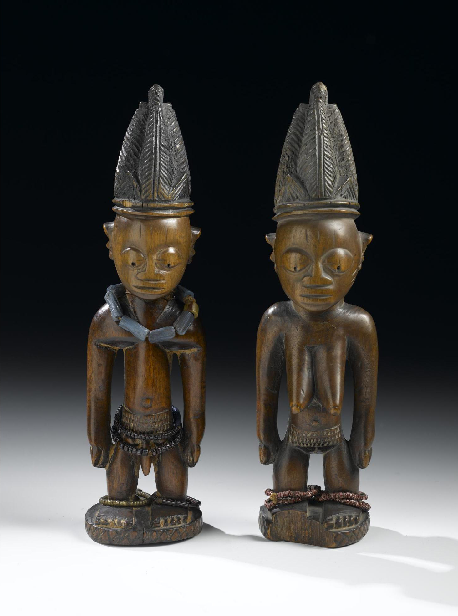 Late 19th-early 20th century male and female ere ibeji figures made from carved and painted wood, wearing high headdresses and strings of beads. Made in Nigeria.