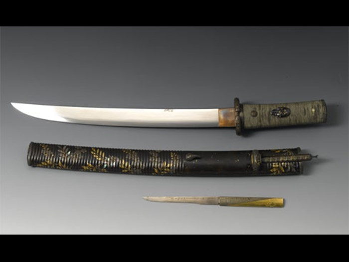 Tanto or dagger, with a curved single-edged steel blade signed in brass inlay, a wooden hilt wrapped in silk cord, and signed shibuichi mounts: Japan, blade by Kunihiro, mounts by Issho.