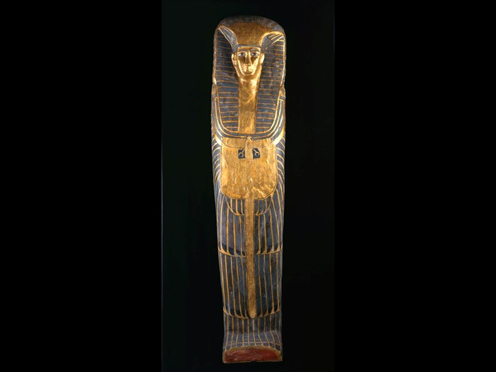 Female coffin: an exceptionally tall coffin with decoration in the rishi-style. The lid has feathered patterning painted in blue with black details on a yellow ground. The owner's face is framed by a striped linen nemes-cloth, a beaded collar with falcon terminals, and a vulture-pectoral.