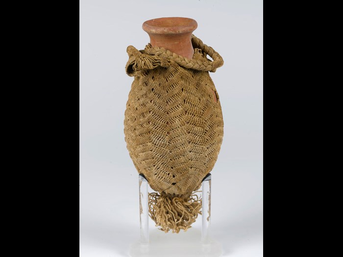 Red burnished flask: one of eight pottery vessels suspended from a stick. Closed, wheelmade flask with out-turned rim, flaring neck and bag shaped body. It is contained in a net bag woven to imitate bead work with two plaited handles and tassels at the bottom.