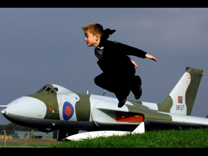 Boy taking flight from bunker in view of Avro Vulcan XM597 at National Museum of Flight, East Fortune Airfield.