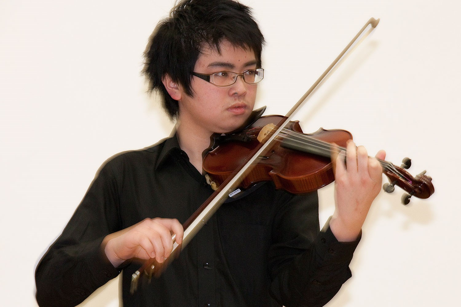 Shetland Young Fiddler of the Year 2009 Chapman Cheng tries out the Shetland fiddle.