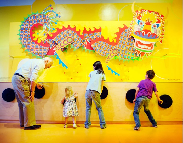 Grandfather and children making a model Chinese dragon dance in the Imagine gallery